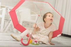 演奏茶会的小女孩坐在伞下 免版税库存照片