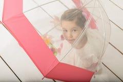 演奏茶会的小女孩坐在伞下 免版税库存图片