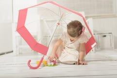 演奏茶会的小女孩坐在伞下 库存图片