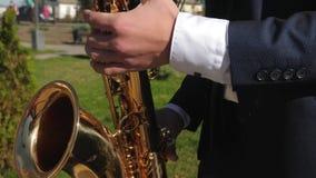 演奏萨克斯管爵士音乐的一个人 无尾礼服戏剧的萨克斯管吹奏者在金黄萨克斯管 生活表现 概念  股票视频