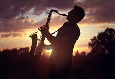 演奏萨克斯管的萨克斯管吹奏者反对日落 免版税库存图片