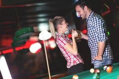 演奏落袋撞球的夫妇饮用的啤酒在日期 免版税库存图片