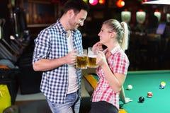 演奏落袋撞球的夫妇饮用的啤酒在日期 免版税图库摄影