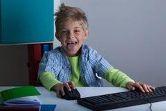 演奏计算机的微笑的男孩 免版税库存图片