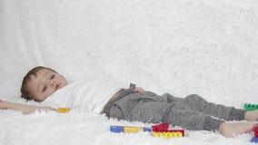 演奏说谎在白色长沙发的愉快的儿童男孩,反对色的玩具背景,移动的腿 股票录像