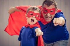 演奏超级英雄的父亲和儿子户外在天时间 库存照片