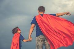 演奏超级英雄的父亲和儿子户外在天时间 免版税库存照片