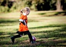 演奏足球年轻人的女孩 图库摄影
