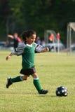 演奏足球年轻人的女孩 库存照片