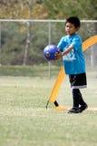 演奏足球年轻人的男孩守门员 免版税库存图片