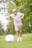 演奏足球年轻人的男孩 免版税库存图片
