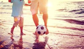 演奏足球海滩夏天概念的父亲儿子 免版税库存照片