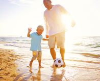 演奏足球海滩夏天概念的父亲儿子 免版税图库摄影