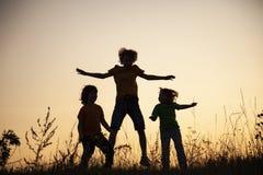 演奏跳在夏天日落草甸的孩子现出了轮廓 免版税库存照片