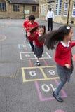 演奏跳房子的小组孩子在学校操场 库存图片