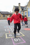 演奏跳房子的小组孩子在学校操场 库存照片