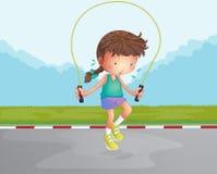 演奏跳绳的一个小女孩在路 免版税库存照片