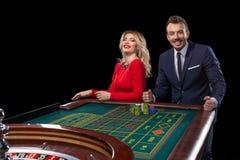 演奏轮盘赌的美好和穿着体面的夫妇在赌博娱乐场 免版税图库摄影