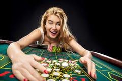 演奏轮盘赌的年轻俏丽的妇女在赌博娱乐场赢取 库存照片