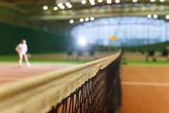 演奏运动员女孩的室内网球场 免版税库存照片