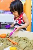 演奏运动沙子的亚裔中国小女孩室内 库存图片