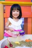 演奏运动沙子的愉快的亚裔中国小女孩室内 免版税库存照片