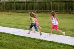 演奏连续姐妹三的女孩公园 免版税图库摄影