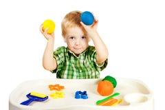 演奏造型黏土玩具,小孩五颜六色的彩色塑泥的孩子 免版税图库摄影