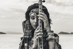 演奏锡塔尔琴的东方服装的美丽的年轻时髦的部族妇女户外 关闭 免版税库存图片