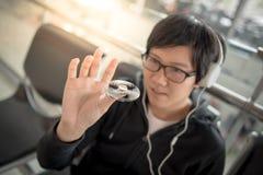 演奏锭床工人坐立不安的年轻亚裔人在机场 免版税库存照片