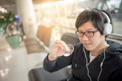 演奏锭床工人坐立不安的年轻亚裔人在机场 免版税库存图片