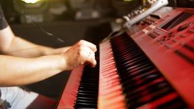 演奏键盘的英俊的音乐家在与背后照明的摇滚乐音乐会在夜总会 影视素材