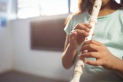 演奏长笛的女孩的中间部分在教室 免版税库存照片