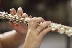 演奏长笛的妇女的手 免版税库存照片