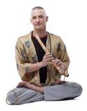 演奏长笛的瑜伽宗师,隔绝在白色 免版税库存图片