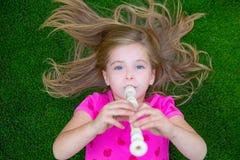 演奏长笛的白肤金发的孩子儿童女孩说谎在草 免版税图库摄影