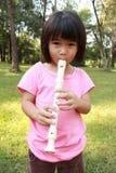 演奏长笛的逗人喜爱的女孩 免版税库存图片