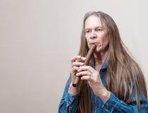 演奏长笛的年长人 免版税库存照片