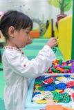 演奏难题的亚裔矮小的中国女孩 免版税库存图片