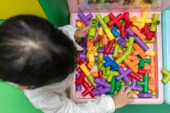 演奏难题管的亚裔矮小的中国女孩 免版税库存图片