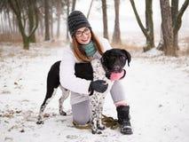 演奏雪冬天的少妇户外拥抱逗人喜爱的被采取的瞎的安装员狗 仁慈和人类概念 库存图片