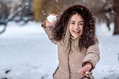 演奏雪球战斗的愉快的妇女在雪天 冬天conce 免版税库存图片