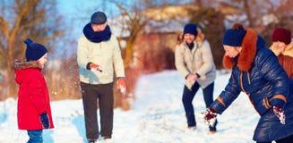 演奏雪球的大愉快的家庭在美好的冬日 免版税库存图片