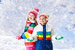 演奏雪的孩子 户外儿童游戏在冬天降雪 图库摄影