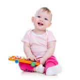 演奏音乐玩具的愉快的婴孩 免版税库存照片