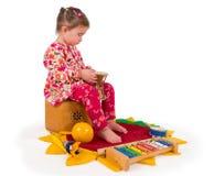 演奏音乐的一个小的小女孩。 免版税图库摄影