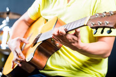 演奏音乐的亚裔吉他弹奏者在录音室 免版税库存照片
