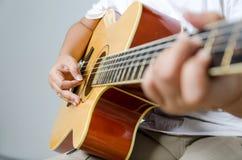 演奏音乐的女性手由声学吉他 免版税库存照片