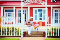 演奏音乐的父亲和儿子,坐台阶 免版税库存照片