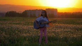 演奏音乐的美丽的少年女孩户外在城市的背景 更加滑稽的情感由日落光做鬼脸剪影 影视素材